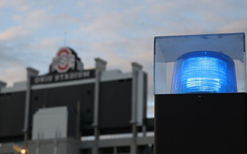 a light atop a police cruiser, with Ohio Stadium in the background
