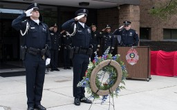 officers saluting at the memorial service in front of Blankenship Hall