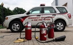 three fire extinguishers on pavers, in front of a emergency response vehicle
