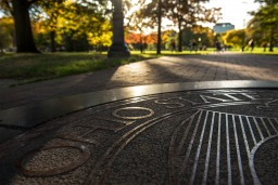 late afternoon photo of the university seal at the east end of the long walk, looking toward the library