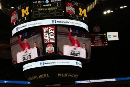 central display board about the ice at the hockey game, displaying Officer Shaffer waving to acknowledge the applause