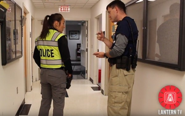 a police woman and a man in a hallway, discussing safety techniques