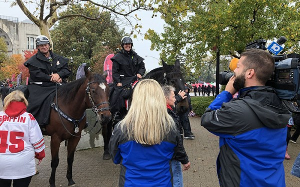 police officers atop police horses, with students gathered around